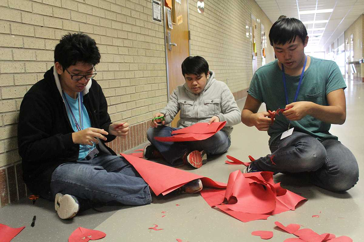Sophomore Kevin Le and juniors Kevin Nguyen and Don Nguyen create decorations and notes for to put on the wall in I Hall.